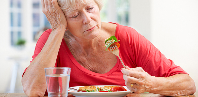 Older woman is playing with her food and expressing a loss in appetite in her face
