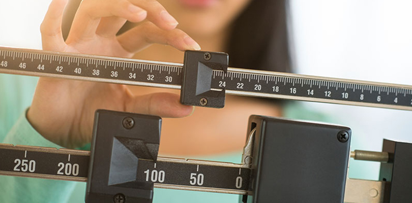 Woman is standing on a sliding scale and determining her weight