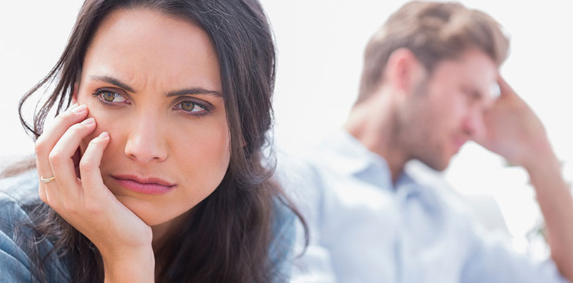 A man and woman are looking away from each other frustrated
