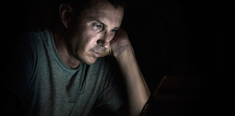 Man sitting in the dark looking at his laptop screen