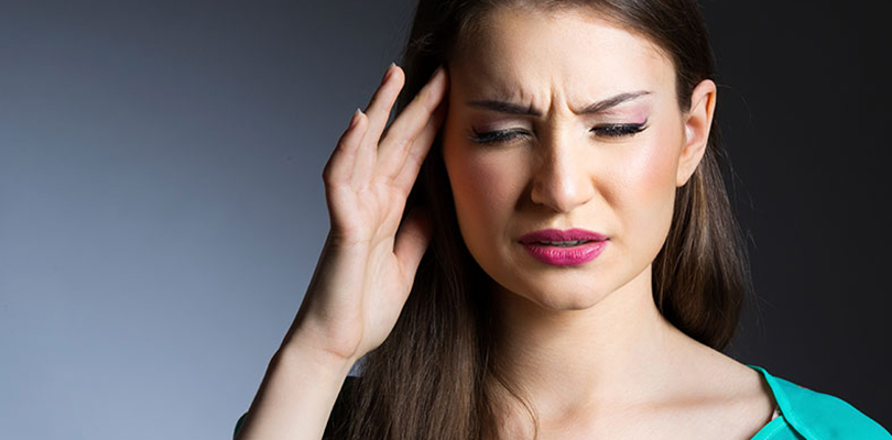A woman is dealing with a migraine or headache and holds hand to her head