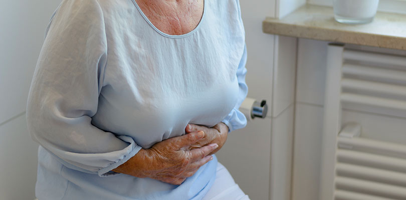 Older woman is clenching her stomach
