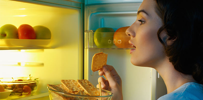 A woman is looking into the fridge for some snacks