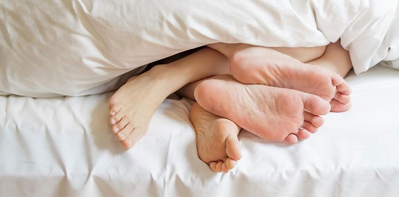 Two people are laying in bed with their feet intwined