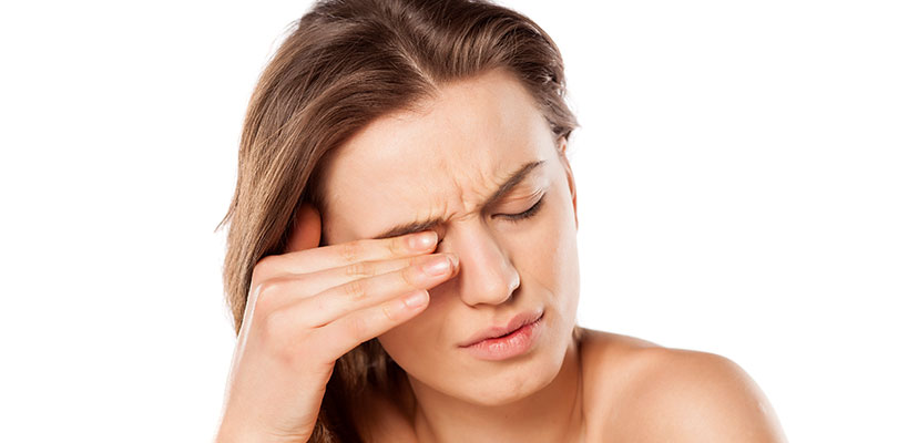 A woman places her fingers on top of her eyelid