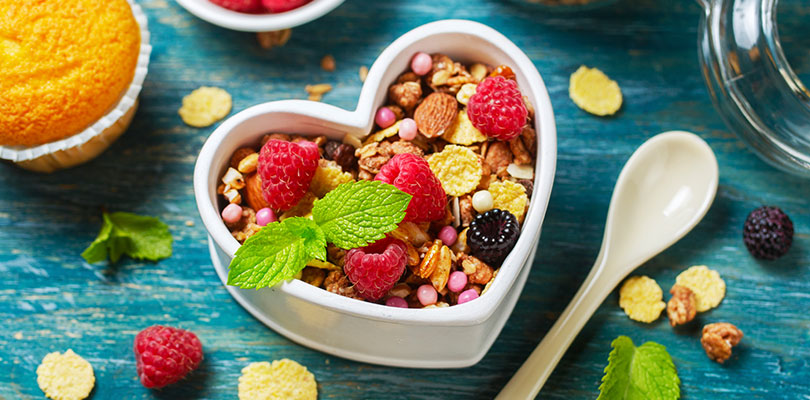 A yogurt and granola parfait is in a heart shaped bowl