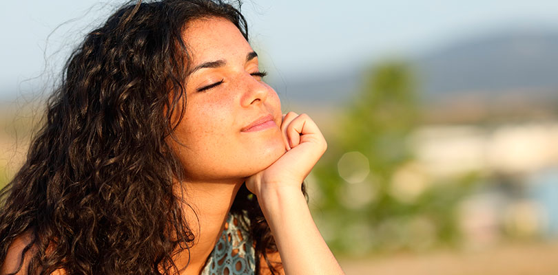 Young woman smiling with her face in the sun