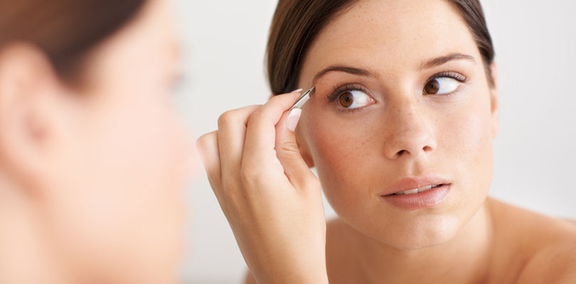Young woman plucks her eyebrows in front of a mirror