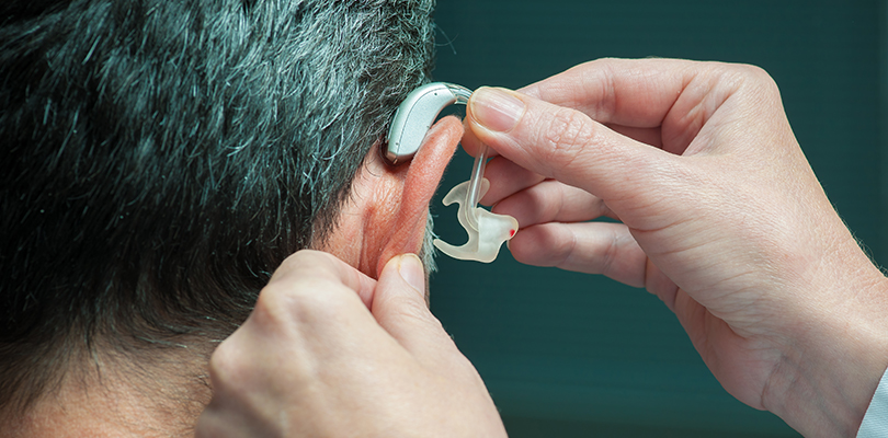 Hands putting a hearing aid on a man