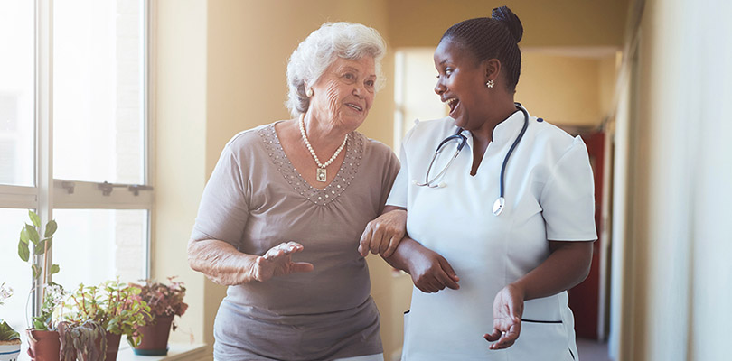 A caregiver and an elderly woman are walking and talking in an assisted living home