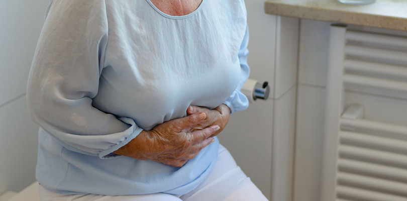 A woman is holding her nauseous stomach