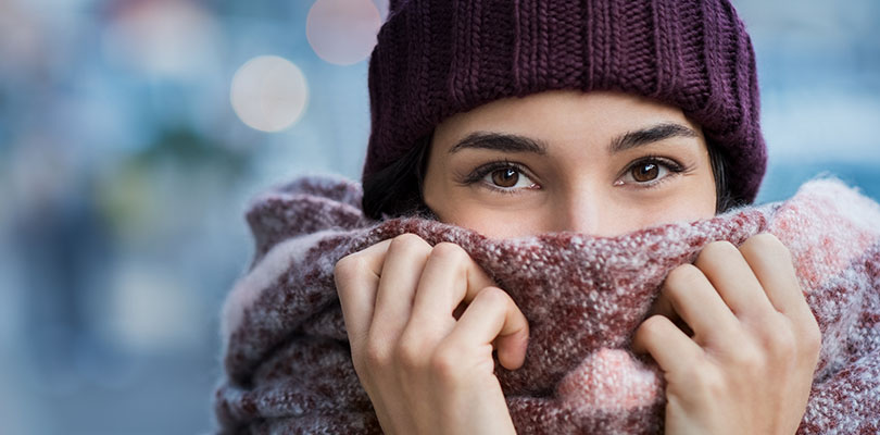 A woman is holding her scarf to her face