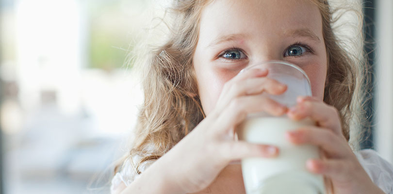 A young is drinking a glass of milk, which is a calcium-rich drink