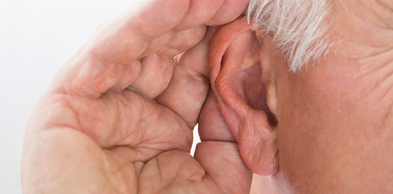 An older gentleman is cupping his ear