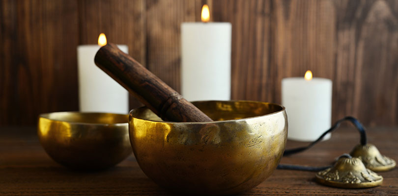 Candles, ting bowls and other meditation tools are on a table.