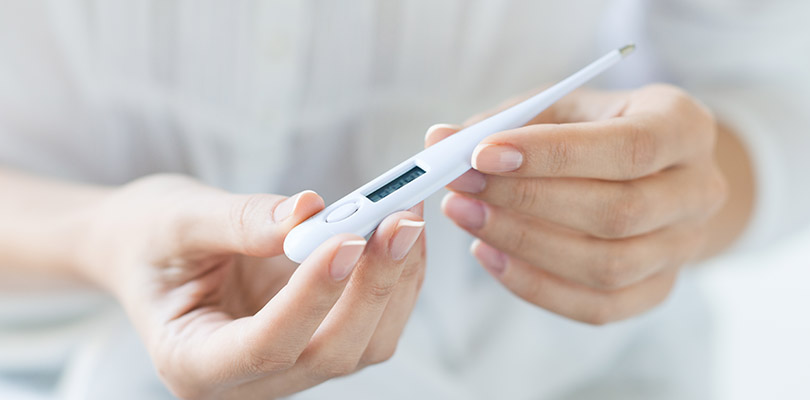 A person is holding a mouth thermometer
