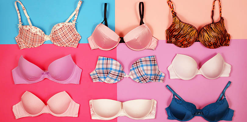 Different sizes of bras on a colored background