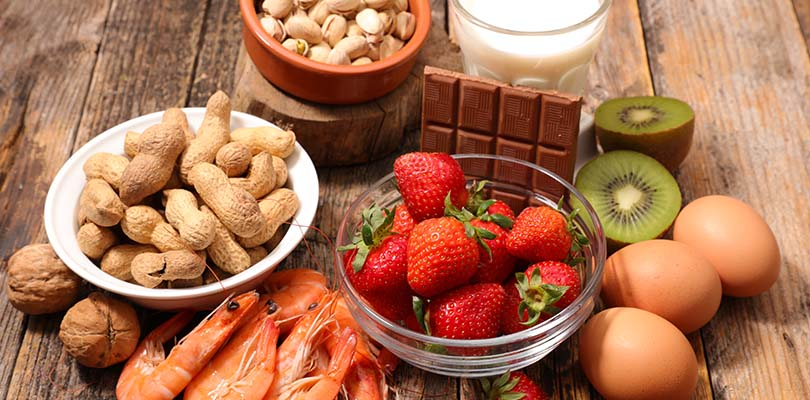 Strawberries, shellfish, peanuts, tree nuts, eggs and milk are on a table