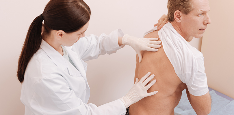 A doctor checking out a man's back
