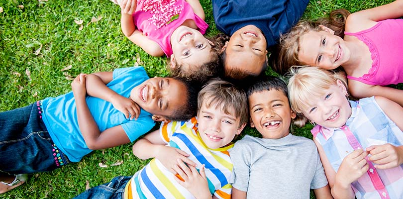 A group of children are laying in a circle