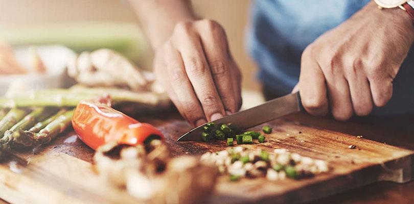 A man is cutting green onions on a cutting board