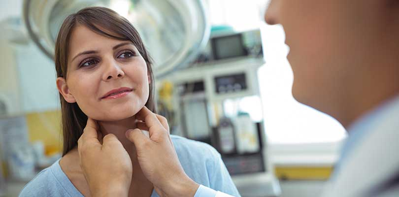 A woman having her neck examined by a doctor