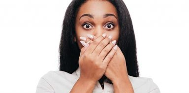 A woman covering her mouth after a hiccup