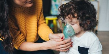 A woman holding an oxygen mask up to a child.