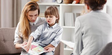Mother with intellectual disabled child with drawing during consultation with psychotherapist