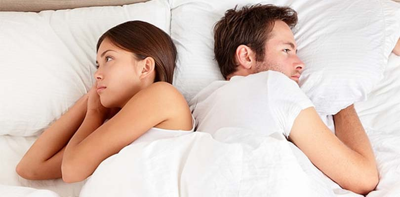 A man in a woman turned away from each other in a bed.