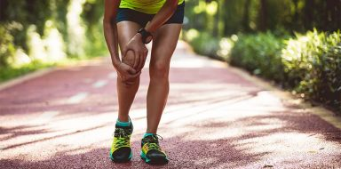 A runner holding her knee on a path outside.