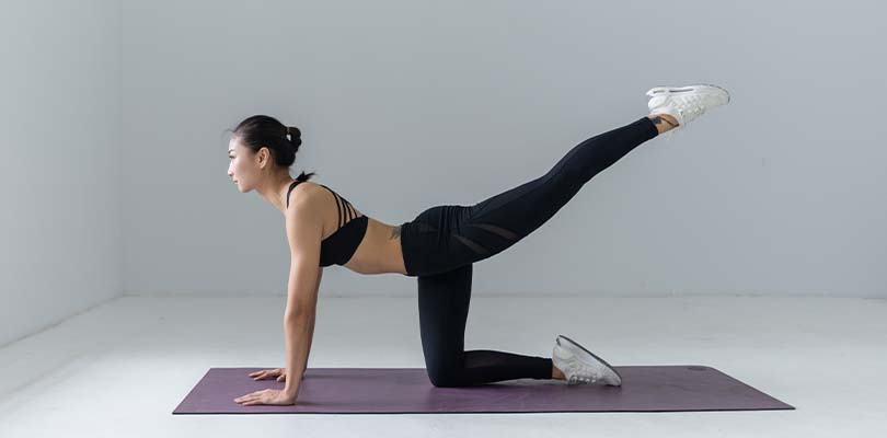 A lady stretching on a purple yoga mat.