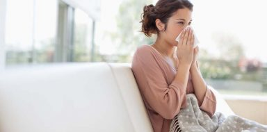 A woman sitting on the couch blowing her nose.