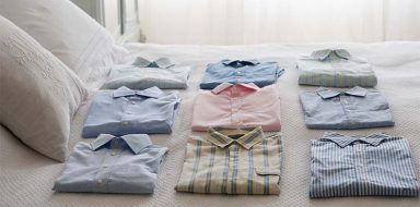 Folded dress shirts laying neatly on a bed.