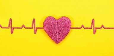 A pink heart in front of a yellow background with heart beat monitor levels.