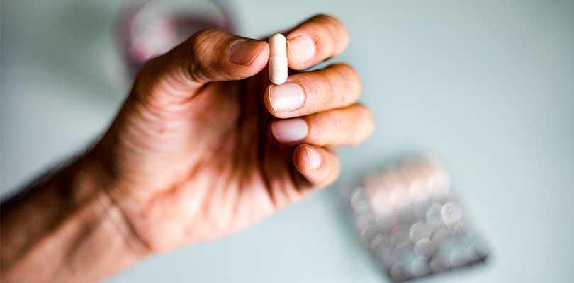 A person holding a pill.