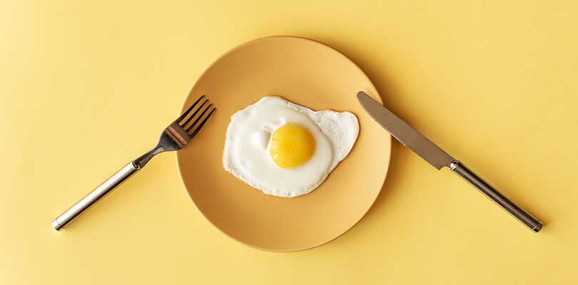 A sunny-side-up egg on a yellow plate with a fork and knife against a yellow background.